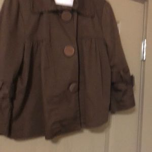 Woman's short brown jacket with large buttons.
